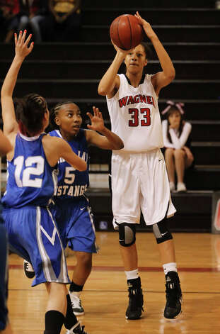 Wagner's Arielle Roberson (33) shoots the ball as John Jay's Antania Newton (05) defends. / kmhui@express-news.net