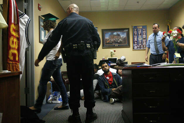 DREAM Act supporters a led to be arrested by San Antonio Police officers. The group refuse to leave until the Senator agreed to support the immigration reform measure that would provide a path to citizenship for immigrants brought to the country illegally under the age of 16 who go on to complete two years of college or military service. / glara@express-news.net