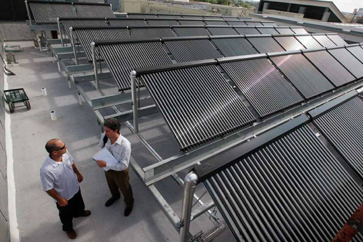 Cinco Solar's Hollis Fitch (left) and Hugh Daschbach stand by solar thermal panels on the roof of the Bexar County Jail Annex. The county expects to save up to $50,000 a year on utility bills at the facility.
