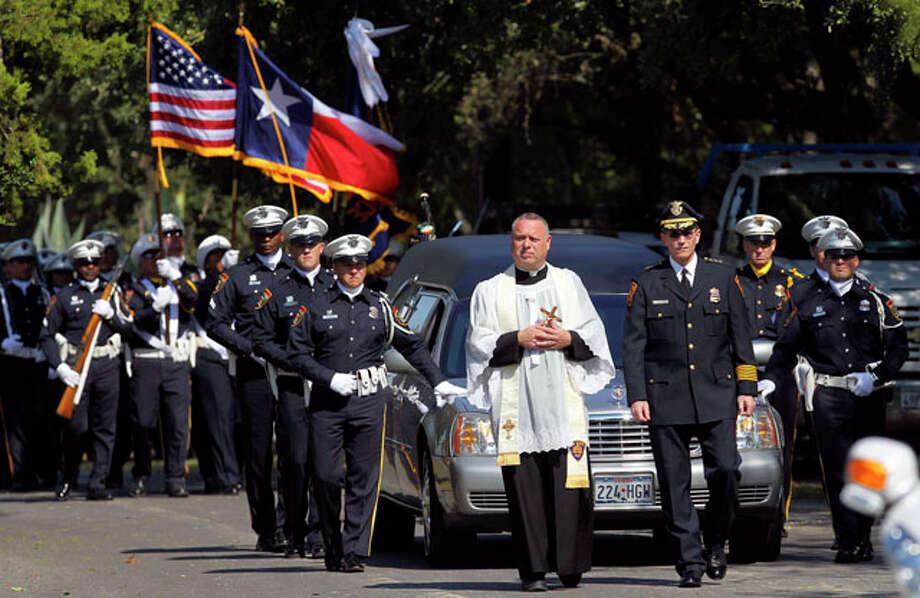 Father Jimmy Drennan (left, in white) and San Antonio Police Chief William McManus (right) lead the procession during the funeral of San Antonio Police Officer Sergio Antillon at Resurrection Cemetery Tuesday November 2, 2010. Antillon died October 29, 2010 from injuries sustained after he was hit by an alleged drunk driver on October 14. / jdavenport@express-news.net