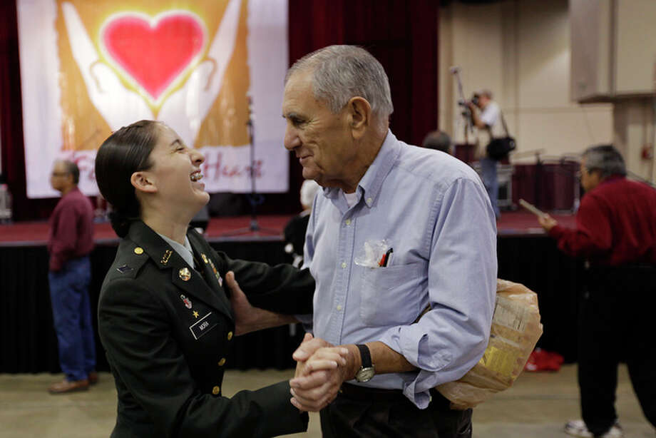 Bill Pope enjoys a dance with Lee High School ROTC Lt. Col. Rosa Mora during the annual Raul Jimenez Thanksgiving Dinner at the Henry B. Gonzalez Convention Center, Thursday, Nov. 25, 2010. By the end of the day, approximately 25,000 plates will have been served at the event that was started 31 years ago. / glara@express-news.net