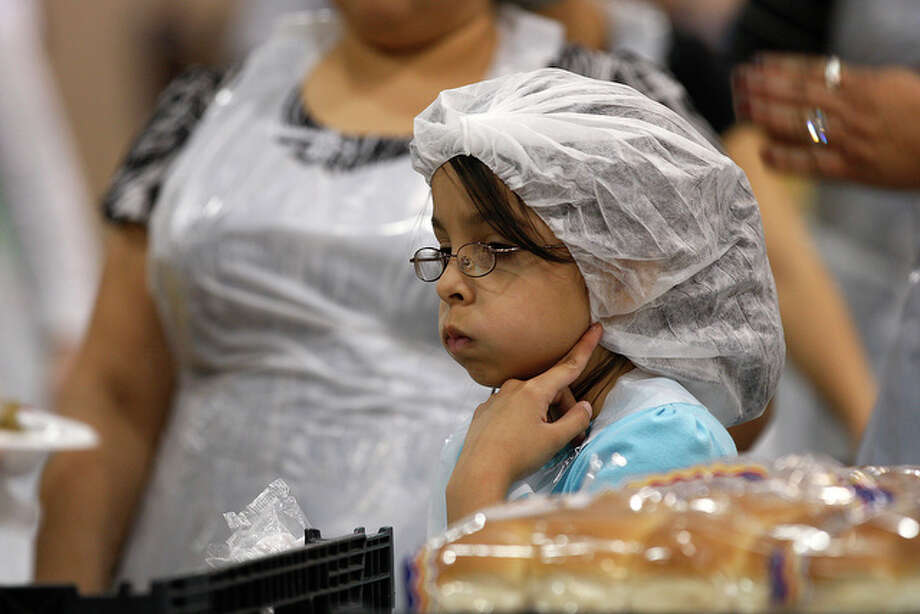 Alondra Villarreal, 8, waits for turkey plates as she helps her mother deliver them to people attending at the annual Raul Jimenez Thanksgiving Dinner. / glara@express-news.net