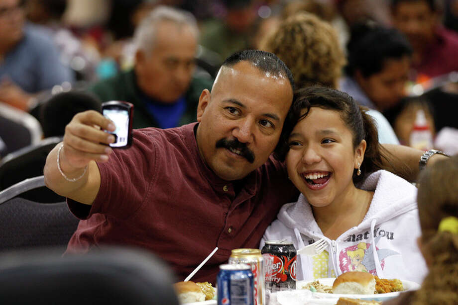 Alex Soria takes a picture with his daughter, Ariana, 12, at the annual Raul Jimenez Thanksgiving Dinner. He was texting the photograph to his son in Alaska. / glara@express-news.net