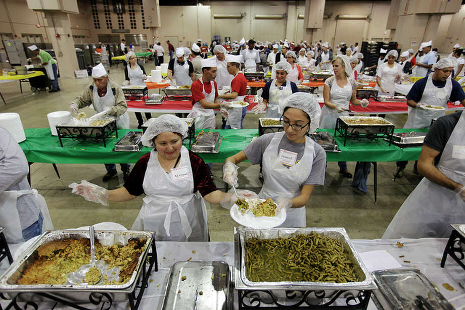 Rosemary Galvan, 55, left, and Jasmine Morales, 19, are part of 4,000 volunteers helping out during the annual Raul Jimenez Thanksgiving Dinner at the Convention Center, Nov. 25, 2010. / glara@express-news.net