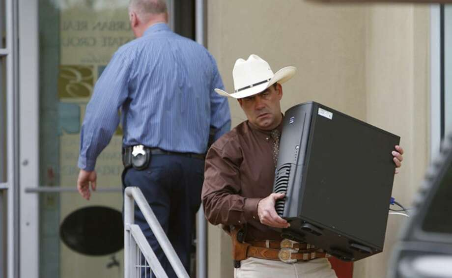 Texas Rangers along with the Bexar County District Attorney's Office remove items from a business affiliated with Gary Cain as part of an investigation.