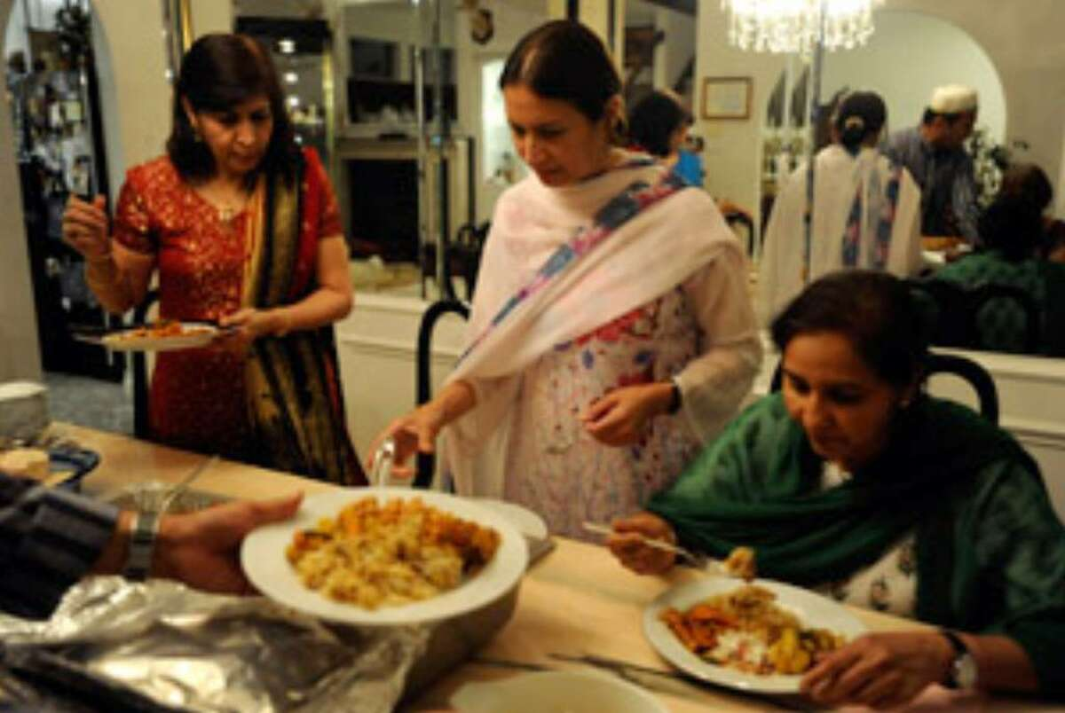 Dinner is served in the home of Raiqua Arastu (left) on the first day of Ramadan, the Islamic holy month in which Muslims are asked to fast from dawn until dusk.
