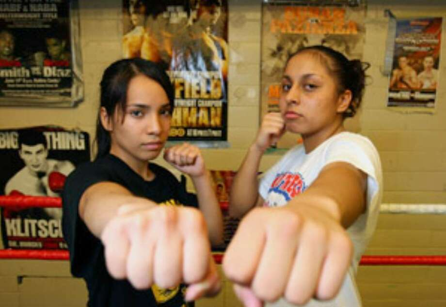 San Antonio boxers Ashlee Reyes, 19, (left) and Selina Barrios, 16, pose at San Fernando Gym. Both hope to qualify for the 2012 Olympics.