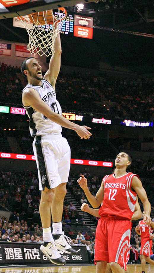 Spurs' Manu Ginobili dunks as Rockets' Kevin Martin looks on Saturday Nov. 6, 2010 at the AT&T Center. The Spurs won in overtime 124-121. / eaornelas@express-news.net