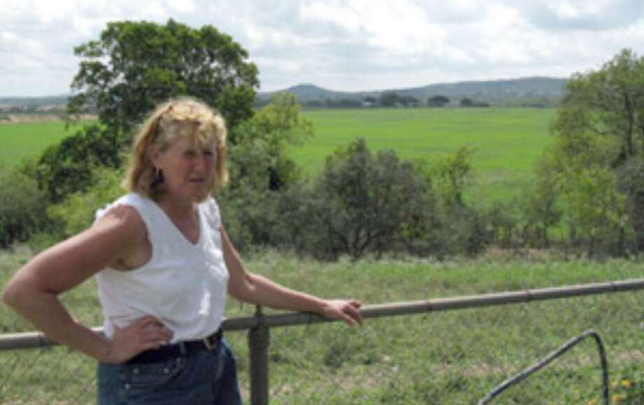 Kerr County resident Mary Matthews is fighting plans for a high-end RV resort planned on the field shown behind her, which is beside her home on Texas 27.