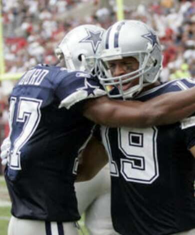 Cowboys receiver Miles Austin (right) hugs Sam Hurd after scoring in the season-opening win over the Buccaneers.