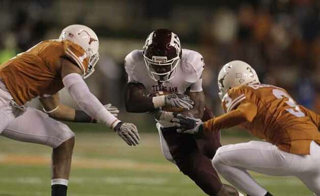 Texas A&M Aggies running back Cyrus Gray (32) runs the ball against Texas Longhorns linebacker Keenan Robinson (1) and  cornerback Curtis Brown (3)during the second half of the University of Texas-Texans A&M college football game at Texas Memorial Stadium, Nov. 25, 2010, in Ausitn. Texas A&M won the game 24-17. / Houston Chronicle