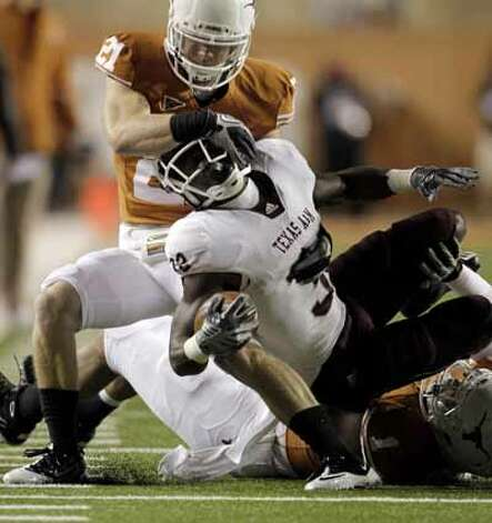 Texas A&M running back Cyrus Gray (32) gets his helmet turned by Texas Longhorns safety Blake Gideon (21) during the first half of an NCAA college football game, Thursday, Nov. 25, 2010.