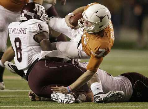 Texas Longhorns quarterback Garrett Gilbert (7) is sacked by Texas A&M Aggies linebacker Garrick Williams (8) during the second half.