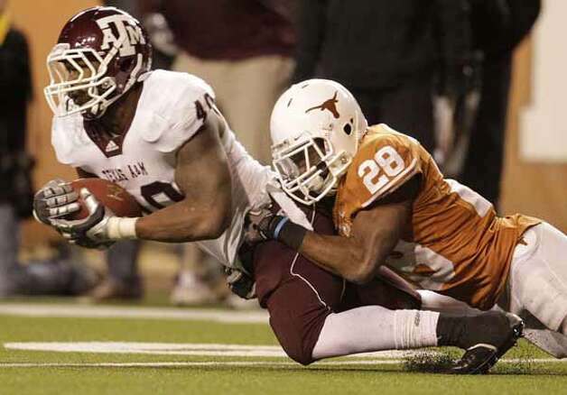 Texas A&M Aggies defensive end Von Miller (40) grabs an interception near the Longhorns end zone stopping their drive late in the fourth quarter of the University of Texas-Texans A&M college football game at Texas Memorial Stadium, Nov. 25, 2010, in Austin. Texas A&M won the game 24-17.