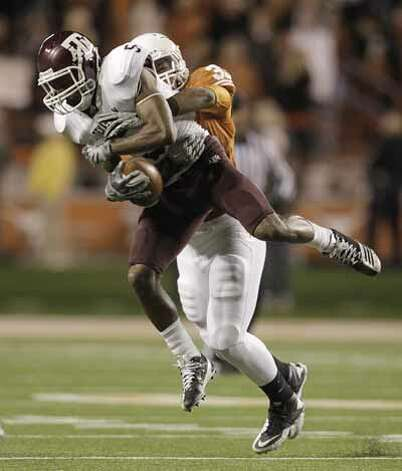 Texas A&M Aggies wide receiver Kenric McNeal (5) catches a pass as Texas Longhorns linebacker Jordan Hicks (33) wraps him up during the second half.