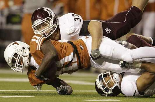 Texas Longhorns wide receiver James Kirkendoll (11) is brought down by Texas A&M Aggies linebacker Michael Hodges (37) and Texas A&M Aggies cornerback Trent Hunter (1) during the first half of the University of Texas-Texans A&M college football game at Texas Memorial Stadium, Nov. 25, 2010, in Austin.