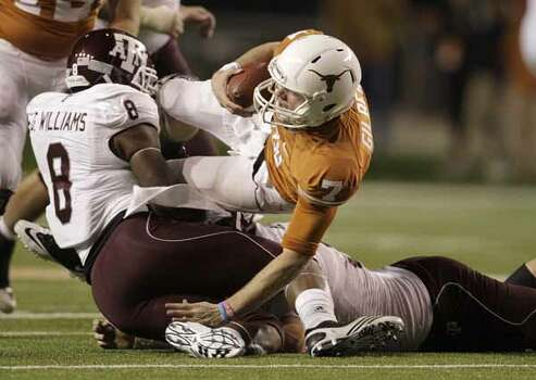 Texas Longhorns quarterback Garrett Gilbert (7) is sacked by Texas A&M Aggies linebacker Garrick Williams (8) during the second half of the University of Texas-Texans A&M college football game at Texas Memorial Stadium, Nov. 25, 2010, in Ausitn. Texas A&M won the game 24-17. / Houston Chronicle