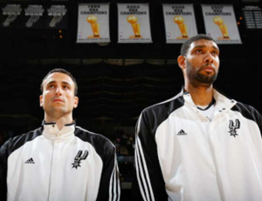 Manu Ginobili (left) and Tim Duncan stand during the national anthem prior to Oct. 9's preseason game with Olympiacos at the AT&T Center.