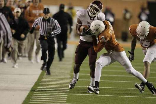 Texas A&M Aggies wide receiver Kenric McNeal (5) gets knocked out of bounds by Texas Longhorns cornerback Curtis Brown (3) during the first half of the University of Texas-Texans A&M college football game at Texas Memorial Stadium, Nov. 25, 2010, in Ausitn. / Houston Chronicle