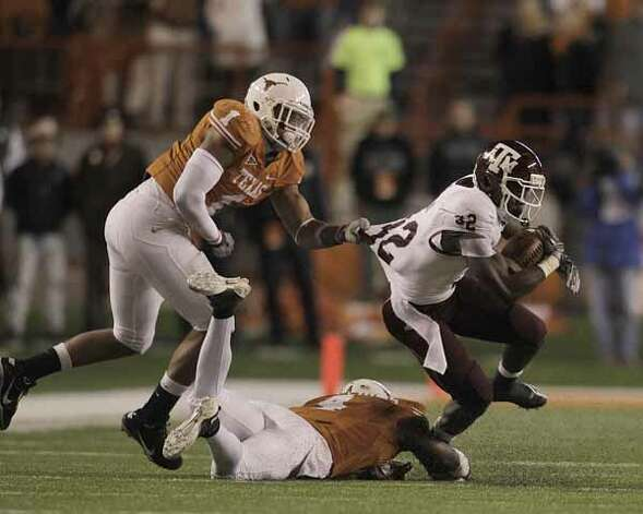 Texas A&M Aggies running back Cyrus Gray (32) gets tackled by Texas Longhorns linebacker Keenan Robinson (1) and cornerback Aaron Williams (4) during the second half.