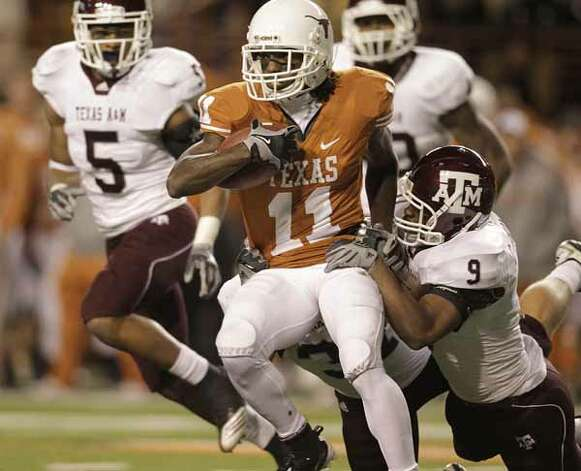 Texas Longhorns wide receiver James Kirkendoll (11) runs with the ball as he gets tackled by Texas A&M Aggies cornerback Charlie Thomas (9) during the second half. / Houston Chronicle