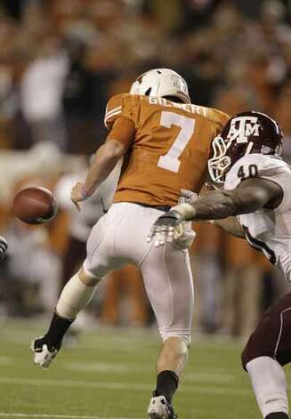 Texas Longhorns quarterback Garrett Gilbert (7) fumbles the ball as he was pressured by Texas A&M Aggies defensive end Von Miller (40) during the second half. / Houston Chronicle