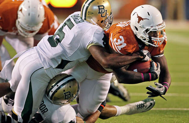 Texas running back Cody Johnson is held up in the middle by Mikail Baker. / © 2010 San Antonio Express-News