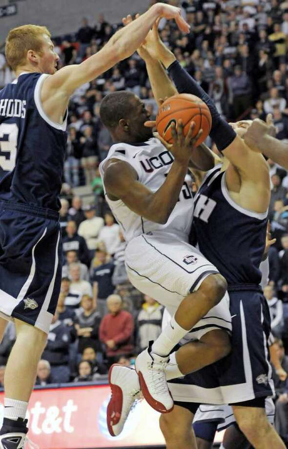 Connecticut's Kemba Walker goes up between New Hampshire's Chandler Rhoads, left, and Dane DiLiegro for a shot in the first half of an NCAA college basketball game in Storrs, Conn., Tuesday, Nov. 30, 2010. (AP Photo/Bob Child) Photo: AP