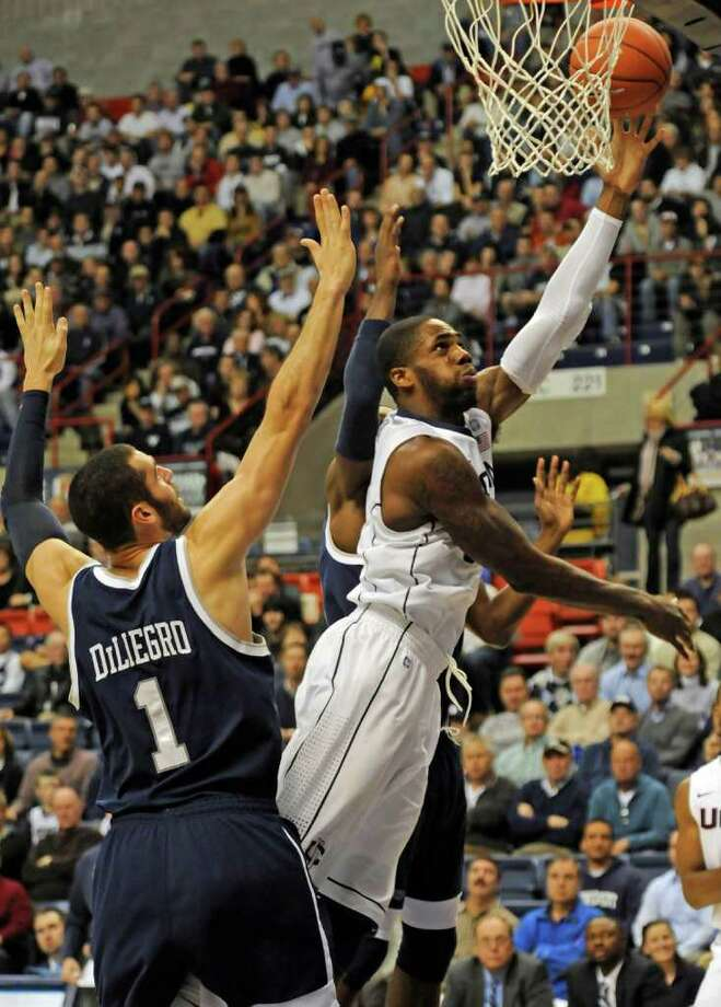 Connecticut's Alex Oriakhi goes up for a shot as New Hampshire's Dane DiLiegro defends in the first half of an NCAA college basketball game in Storrs, Conn., Tuesday, Nov. 30, 2010. (AP Photo/Bob Child) Photo: AP