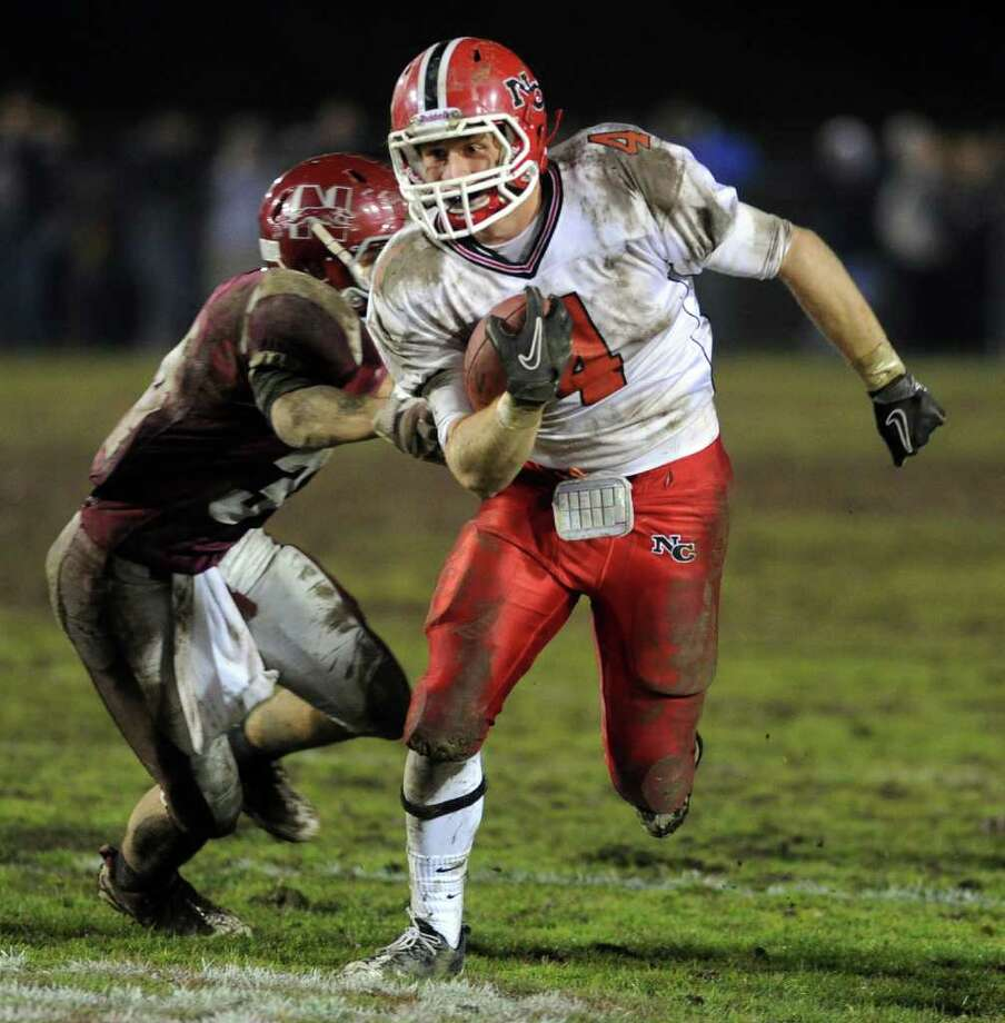 Kevein Macan of New Canaan carries the ball during Tuesday's Class L quarterfinal game at Naugatuck High School on November 30, 2010. Photo: Lindsay Niegelberg / Connecticut Post