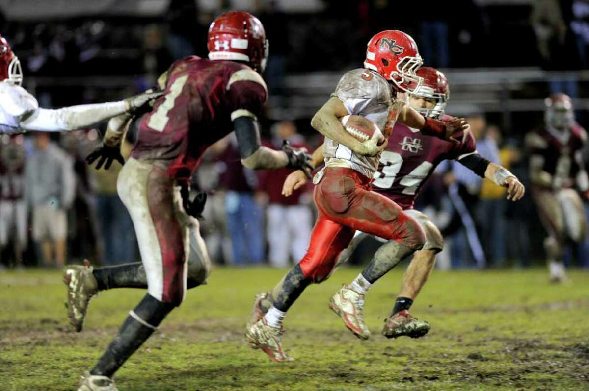 New Canaan's Joseph Costigan carries the ball during Tuesday's Class L quarterfinal game at Naugatuck High School on November 30, 2010.