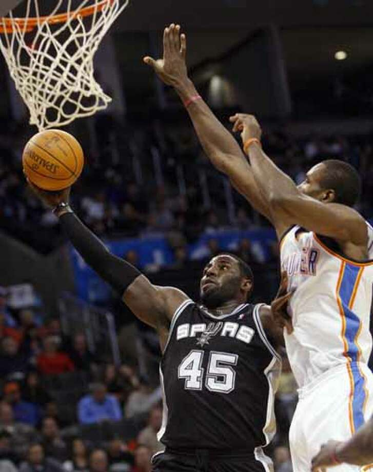 San Antonio Spurs center DeJuan Blair shoots in front of Oklahoma City Thunder forward Serge Ibaka during the second quarter of an NBA basketball game in Oklahoma City, Nov. 14, 2010. Blair finished with 9 points and 11 rebounds in the Spurs 117-104 victory.