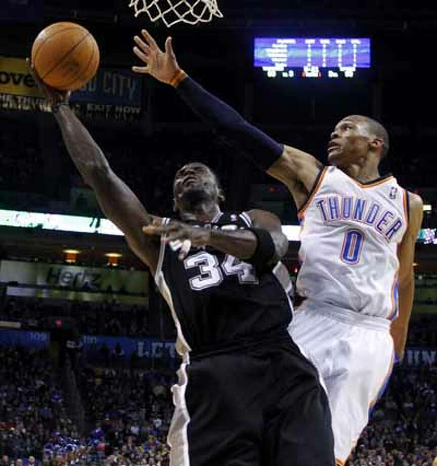 San Antonio Spurs forward Antonio McDyess shoots under the outstretched arm of Oklahoma City Thunder's Russell Westbrook, in the fourth quarter of an NBA basketball game in Oklahoma City, Nov. 14, 2010. San Antonio won 117-104.