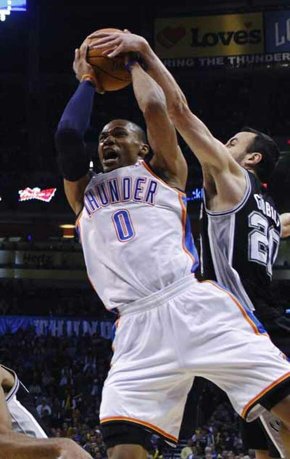 San Antonio Spurs guard Manu Ginobili reaches in to block a shot by Oklahoma City Thunder guard Russell Westbrook during the first quarter of an NBA basketball game in Oklahoma City, Nov. 14, 2010. San Antonio won 117-104.