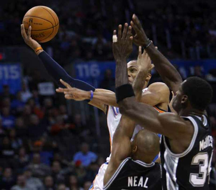 Oklahoma City Thunder guard Russell Westbrook takes a shot while defended by San Antonio Spurs guard Gary Neal and forward Antonio McDyess in the third quarter of an NBA basketball game in Oklahoma City, Nov. 14, 2010. Westbrook had 19 points for the Thunder, but San Antonio won 117-104.