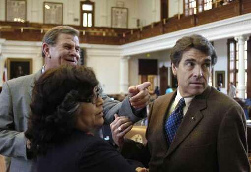 Rep. Edmund Kuempel, R-Seguin, (left) points out the size of the media presence to Gov. Rick Perry while Rep. Norma Chavez, D-El Paso, watches, July 14, 2005, in Austin. / AP