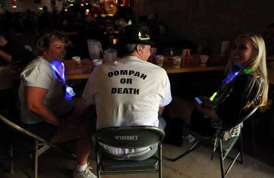 """George Cunningham (center) sports an """"oompah or death"""" t-shirt while chatting with Mandy Medrano (right) and his wife Janet Cunningham (left) during Wurstfest in New Braunfels, Oct. 30, 2010. / Copyright 2010 by Robin Jerstad, Jerstad Photographics LLC, All rights reserved. www.JerstadPhoto.com"""