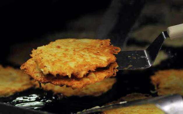 Potatoe pancakes being grilled at the Wurstfest in New Braunfels, Oct. 30, 2010. / Copyright 2010 by Robin Jerstad, Jerstad Photographics LLC, All rights reserved. www.JerstadPhoto.com