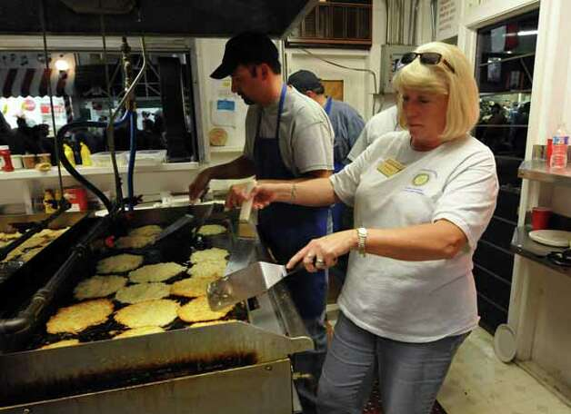 Toya Boyer (foreground)  and Brent Etheredge grill potato pancakes at the Wurstfest in New Braunfels, Oct. 30, 2010. This is the 50th year for the event. / Copyright 2010 by Robin Jerstad, Jerstad Photographics LLC, All rights reserved. www.JerstadPhoto.com