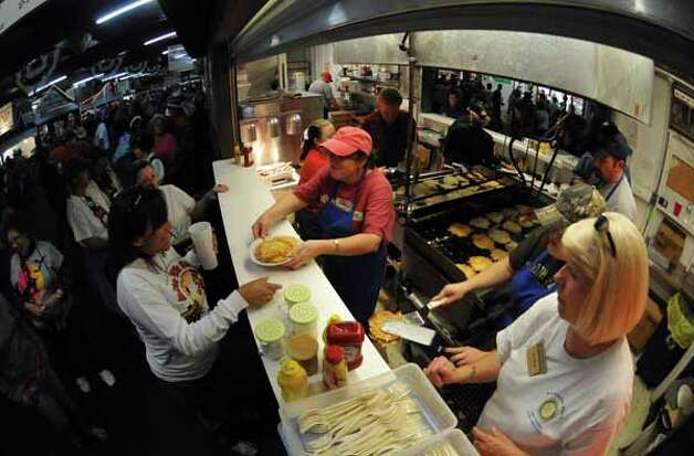 Susan Hankins (center, red hat) serves potato pancakes to Debbie Castilleja as Ashley Hankins (with spatula) and Toya Boyer look on at Wurstfest in New Braunfels, Oct. 30, 2010. / Copyright 2010 by Robin Jerstad, Jerstad Photographics LLC, All rights reserved. www.JerstadPhoto.com