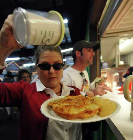 Kathy Ingram adds salt to her potato pancake during the Wurstfest, Oct. 30, 2010. / Copyright 2010 by Robin Jerstad, Jerstad Photographics LLC, All rights reserved. www.JerstadPhoto.com