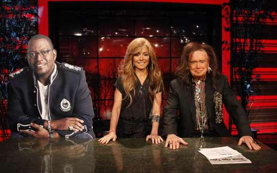 "In this publicity image released by Disney-ABC Domestic Television, co-hosts Regis Philbin, dressed as rocker Steven Tyler (right) and Kelly Ripa, dressed as Jennifer Lopez, are seated next to a cut out of Randy Jackson, completing the judges panel of the singing competition series ""American Idol,"" during the Halloween edition of ""Live! With Regis and Kelly,"" Oct. 29, 2010, in New York."
