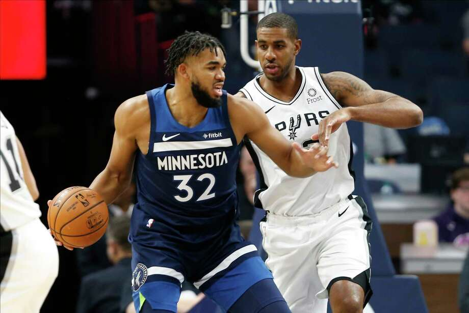 Minnesota Timberwolves' Karl-Anthony Towns forward reaches for a loose ball between San Antonio Spurs guard Patty Mills, right, and Spurs' Jonathon Simmons during the first quarter of an NBA basketball game Tuesday, March 8, 2016, in Minneapolis. Photo: Andy Clayton-King, AP / FR51399 AP