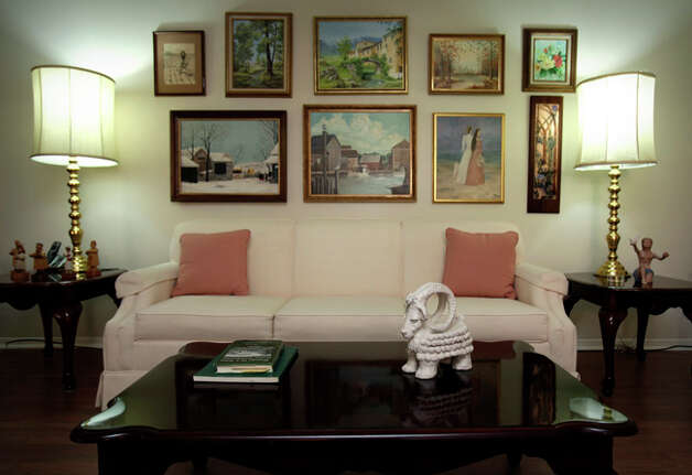 Marti Goeth created several of the paintings above her living room sofa. Her art works are scattered throughout her home. / SAN ANTONIO EXPRESS-NEWS