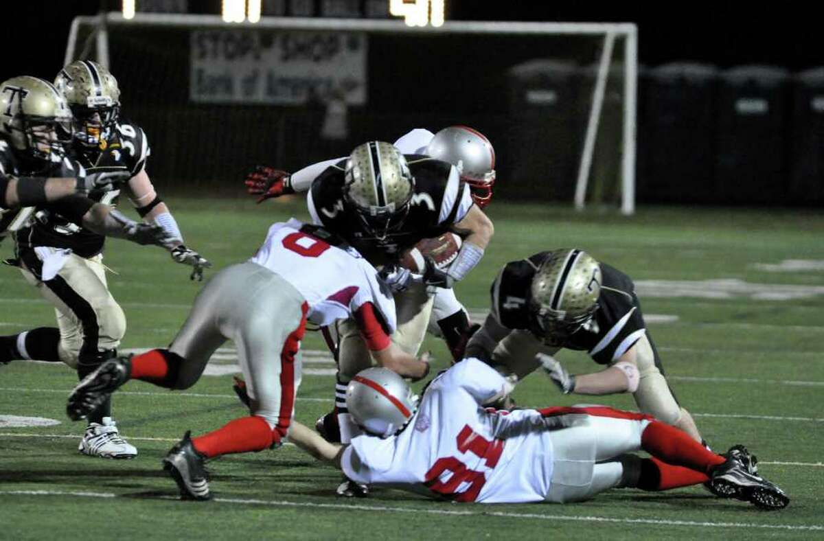 Trumbull's Phil Terio (3) is brought down by a host of Conard defenders during the CIAC quarterfinal football game at Trumbull on Tuesday, Nov. 30, 2010.
