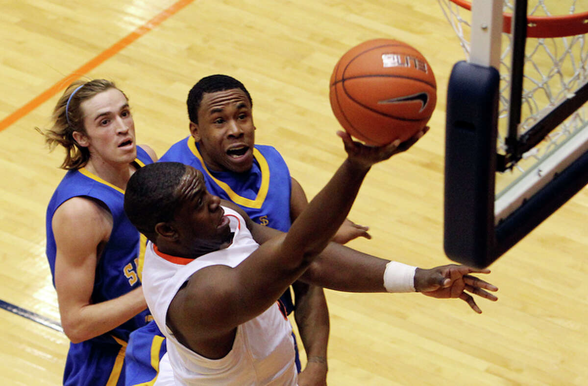 UTSA's Larry Wilkins (front) drives to the basket against San Jose State's Justin Graham (back left) and Calvin Douglas (back right) in a non-conference game at the Convocation Center on Tuesday, Nov. 30, 2010. UTSA defeated the Spartans, 72-63.