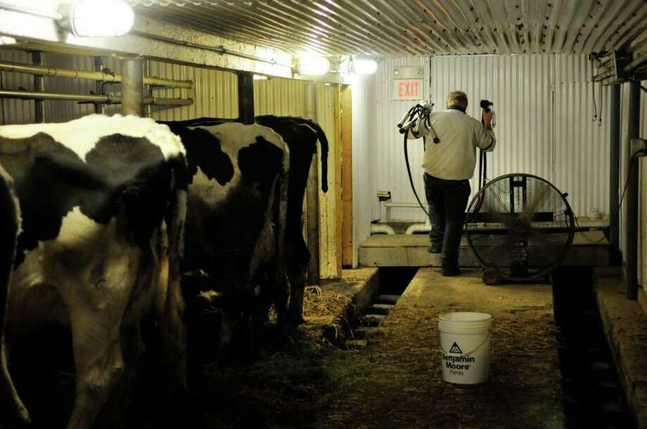 Robert Duncan, owner of Duncan's Dairy Farm carries a milking apparatus back to the storage room after finishing milking his cows at his farm in Brunswick.  (Paul Buckowski / Times Union) Photo: Paul Buckowski / 00011250A