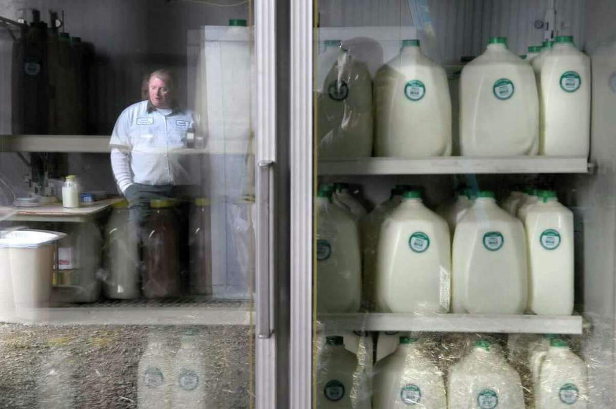 Robert Duncan, owner of Duncan's Dairy Farm is reflected in the cooler inside his store area located in one of the barns at his farm in Brunswick. (Paul Buckowski / Times Union)