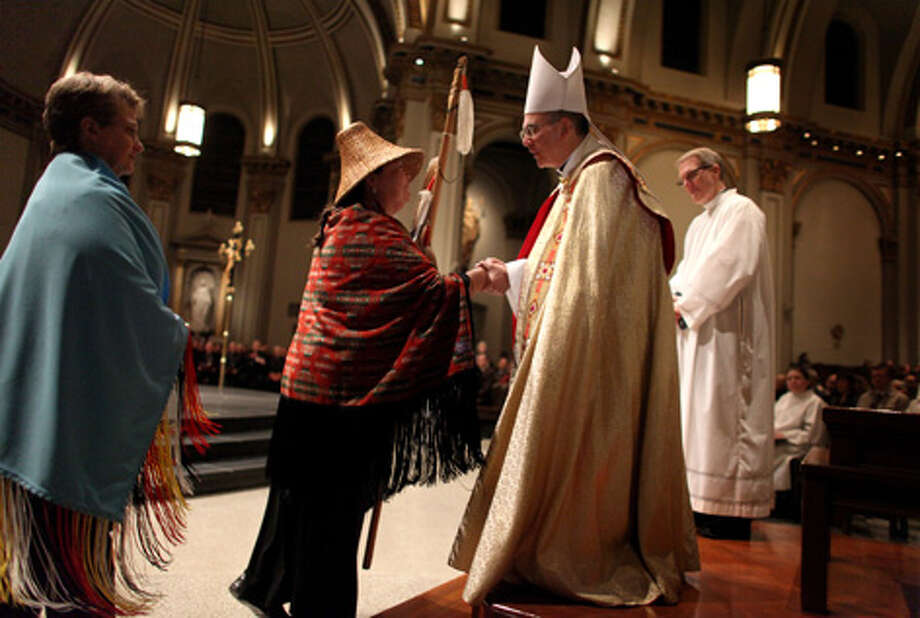 Archbishop-elect J. Peter Sartain is welcomed to the Pacific Northwest by Kay Knott of the Upper Skagit Tribe during a Rite of Reception ceremony at St. James Cathedral on Tuesday in Seattle. Sartain is succeeding Archbishop Alex Brunett as leader of the Archdiocese of Seattle. Photo: Joshua Trujillo/seattlepi.com