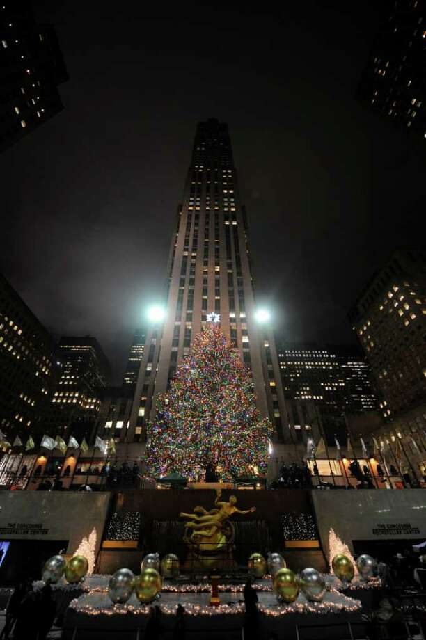 The Rockefeller Christmas tree, a 12-ton, 74-foot Norway spruce covered in 30,000 energy efficient LED lights, is lit in Rockefeller Center in New York, Tuesday, Nov. 30, 2010. (AP Photo/Henny Ray Abrams) Photo: Henny Ray Abrams